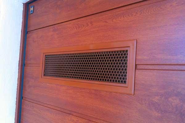 Ventana con marco en color Golden Oak con reja de ventilación